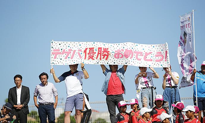 手作りの旗を持って、九州リーグ優勝のお祝いをしてくれたサポーターの皆さん